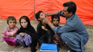 The image shows children displaced by the military operation in North Waziristan receive polio vaccine at a camp in Bannu of the Federally Administered Tribal Areas of Pakistan